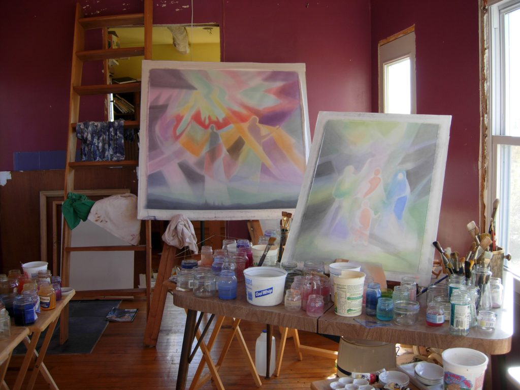 Two colorful paintings shown behind painting supplies.