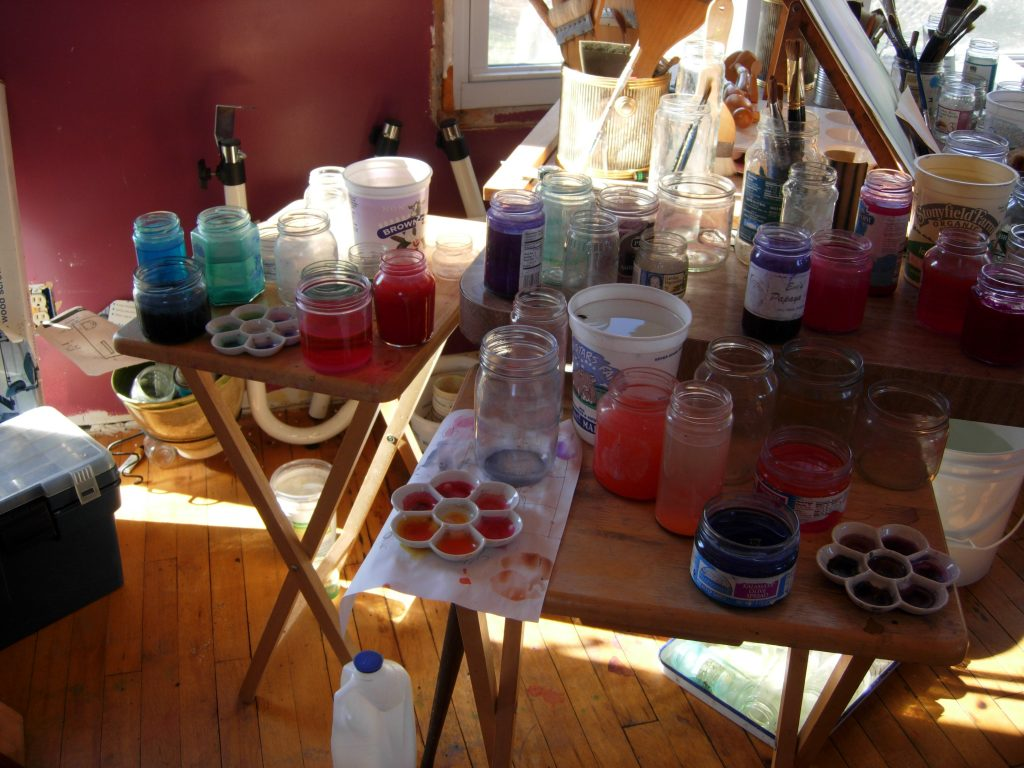 A table covered in jars of paint and brushes.