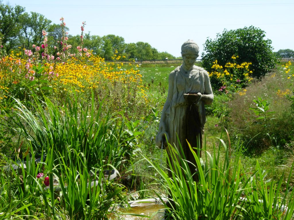 A statue looking down at tall grasses with yellow flowers in the background.